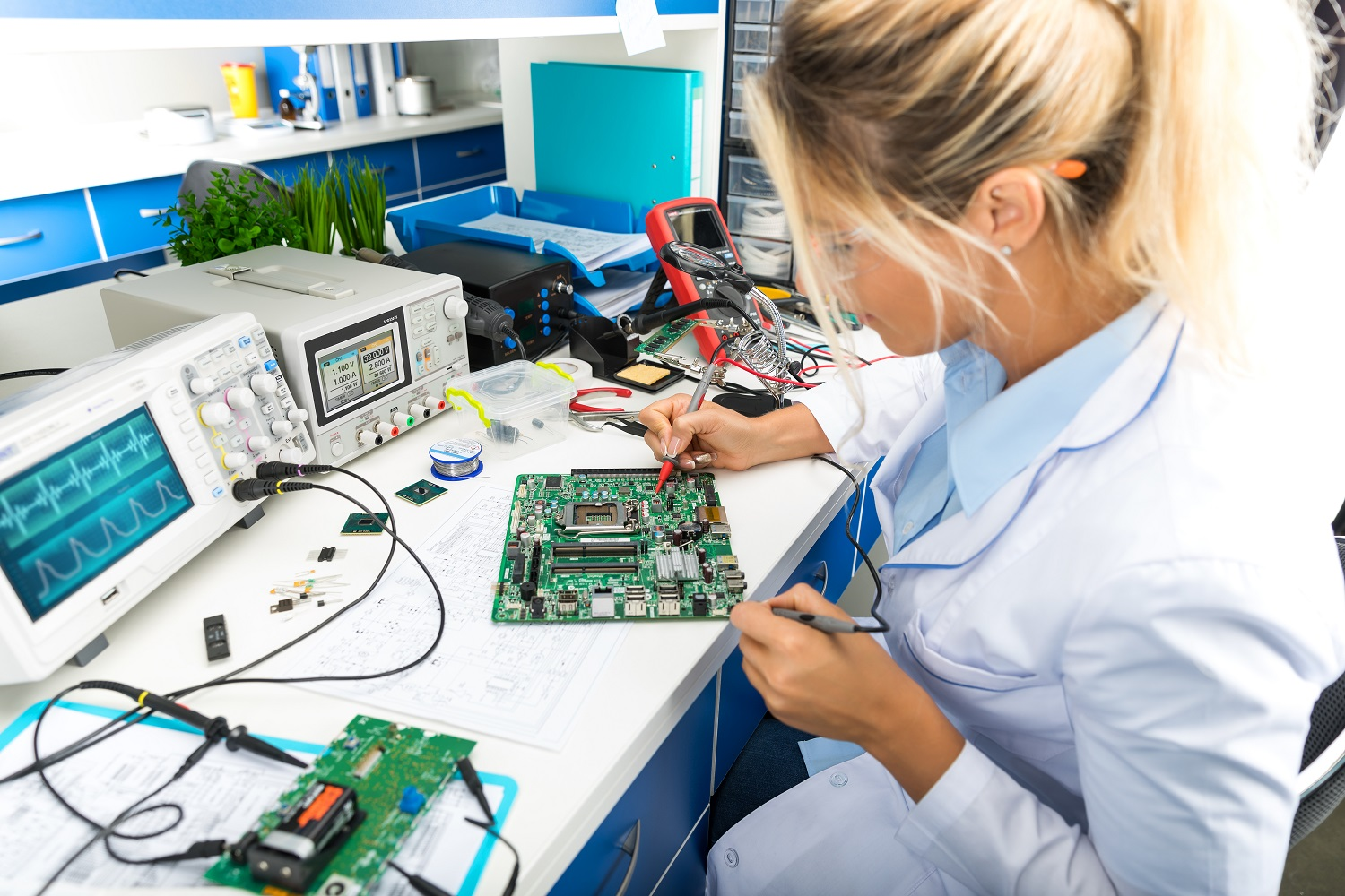 Female electronic engineer testing computer motherboard in laboratory